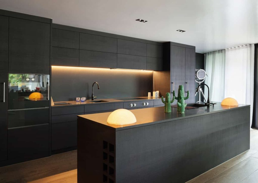 Modern kitchen with black furniture and wooden floor.