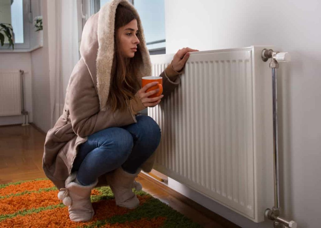 Young woman in jacket squatting beside cold radiator and drinking tea.